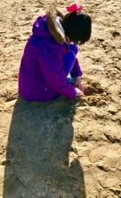 Digging in the sand with the winter coat on.